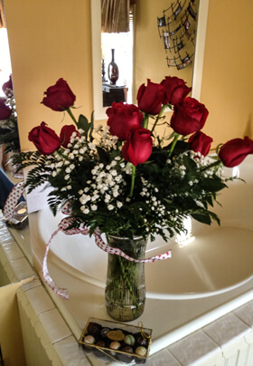 whirlpool tub in honey colored room with a dozen red roses and a package of chocolates