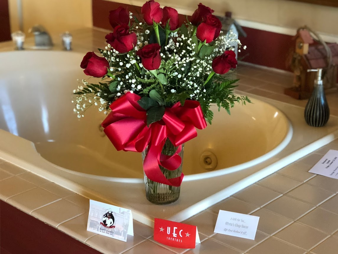 Red roses with a bow in a vase with gift cards on the edge of a jacuzzi tub