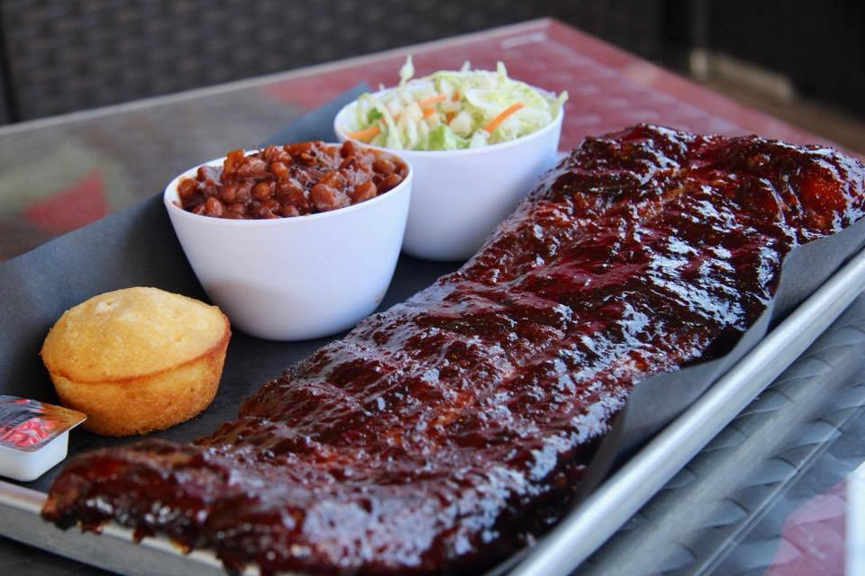 Big rack of barbecued ribs with sides of corn bread beans and coleslaw