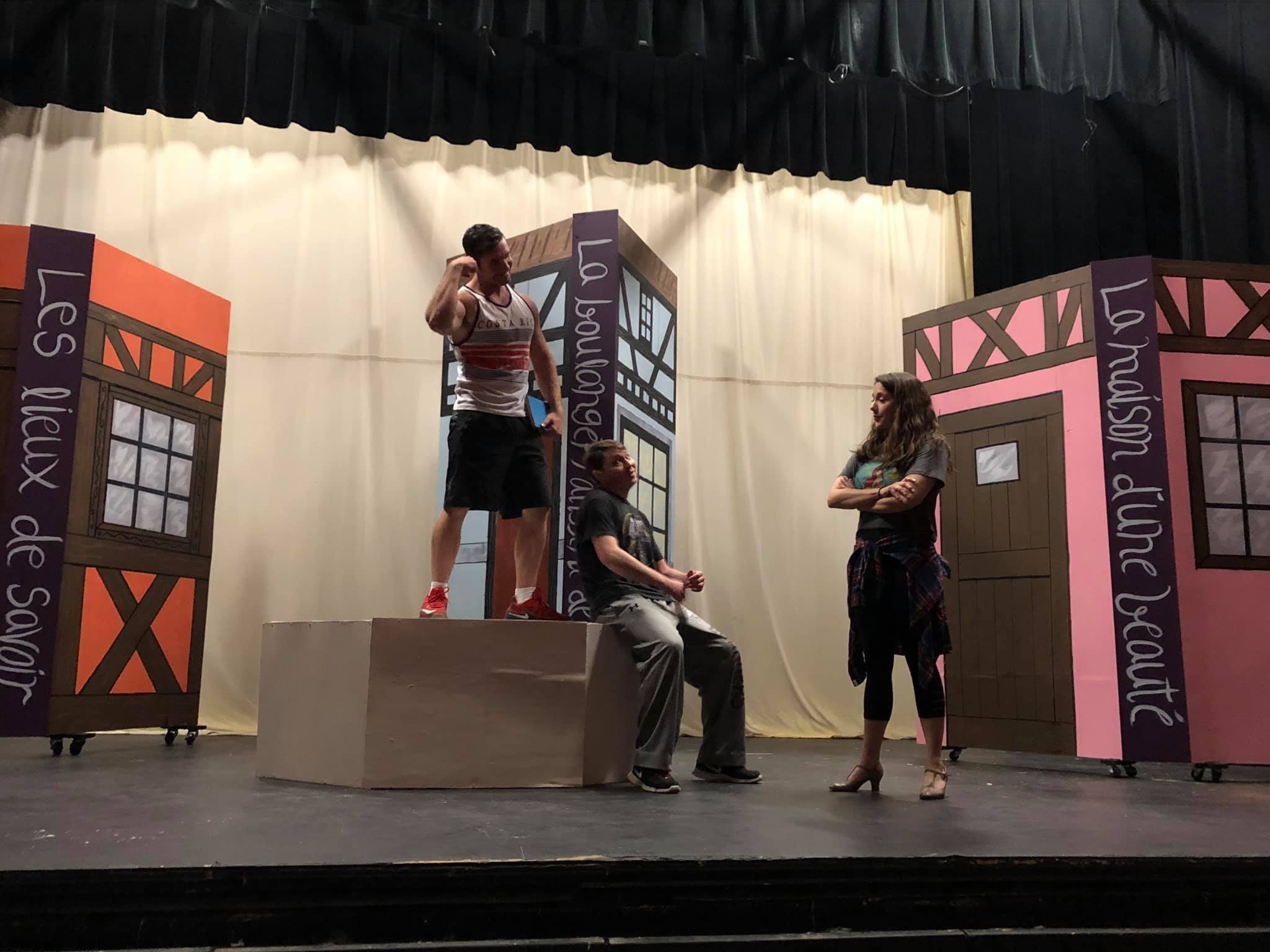 cast practicing musical production on stage