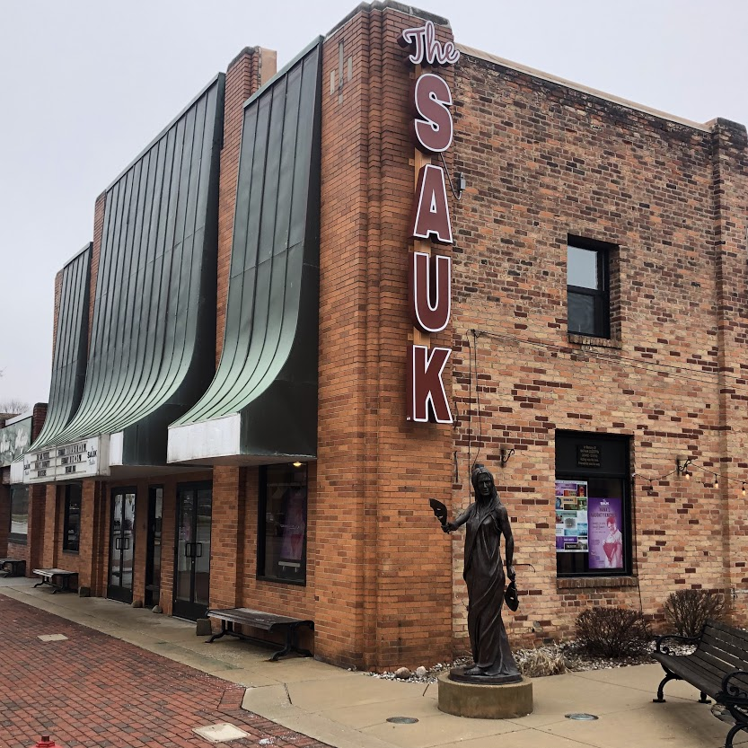"""brick theater building """"the sauk"""" with green awnings and bronze muse statue"""