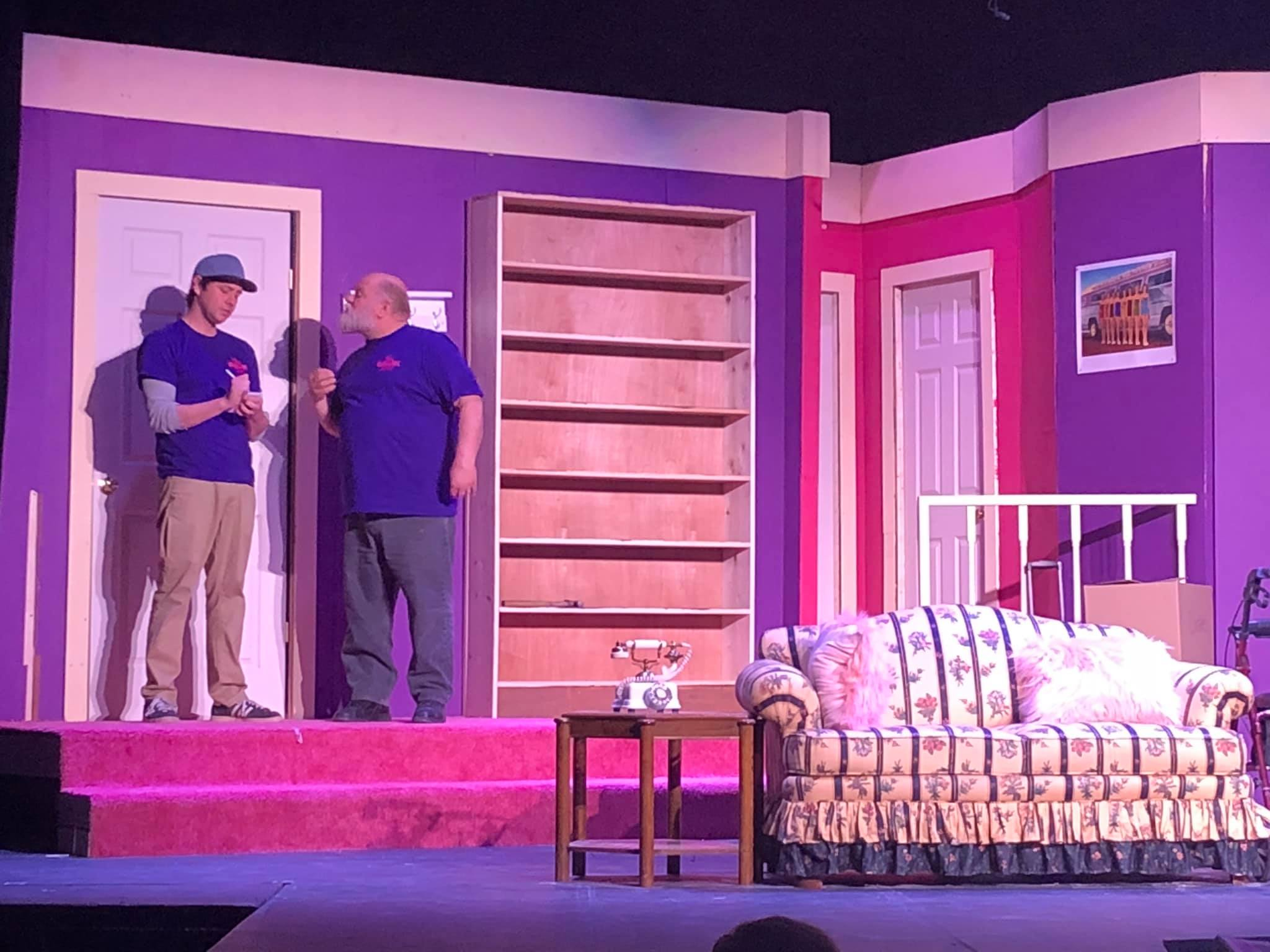 stage set in pinks and purples with 2 male actors wearing blue shirts