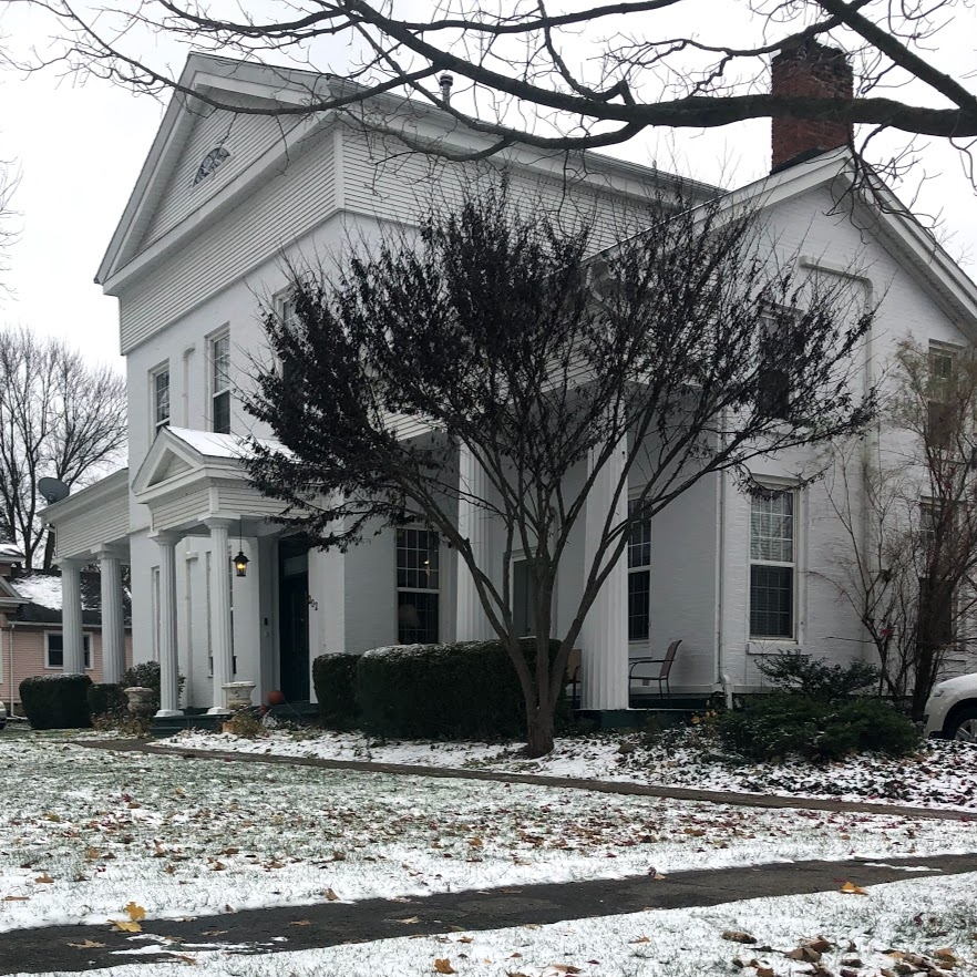 white house with leafless trees on snow covered ground