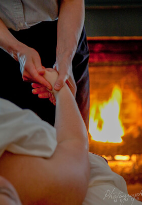 female masseuse wearing gray and black massaging right hand of female in front of fireplace