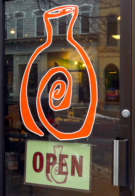 orange logo painted on glass window depicting a paint your own pottery studio