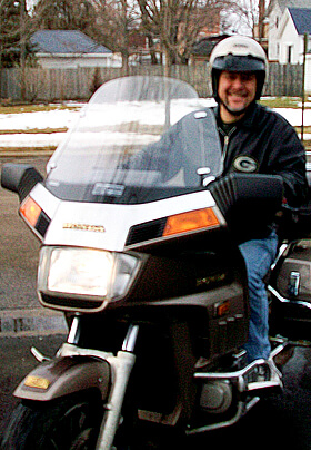 man in black leather jacket riding a goldwing motorcycle with full wind shield