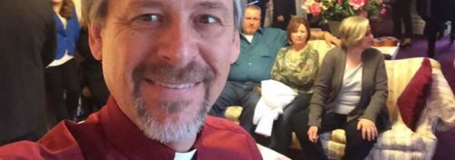 officiant in red shirt with religious collar in living room with people