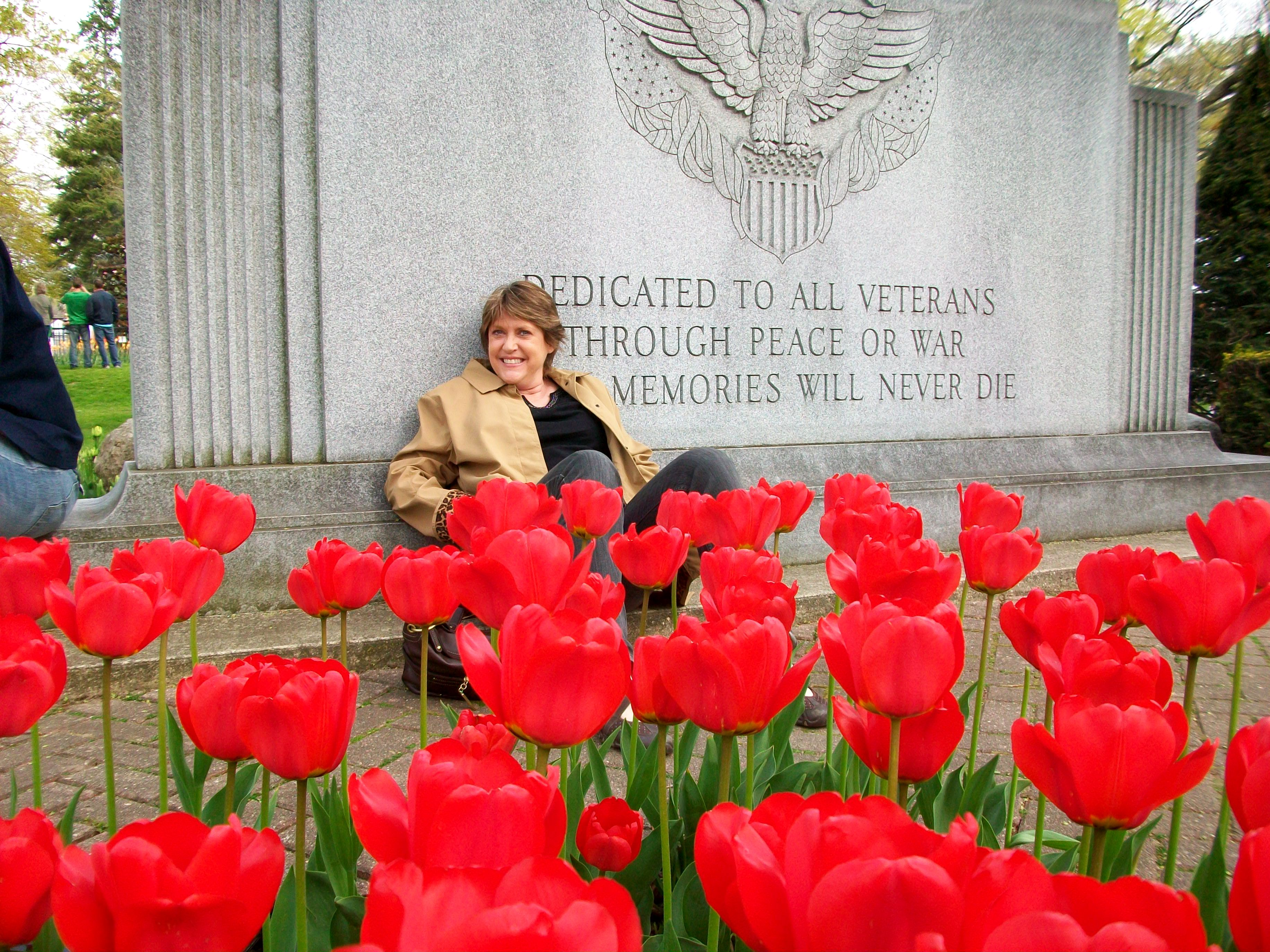 woman sitting against monument behind a bed of red tulips