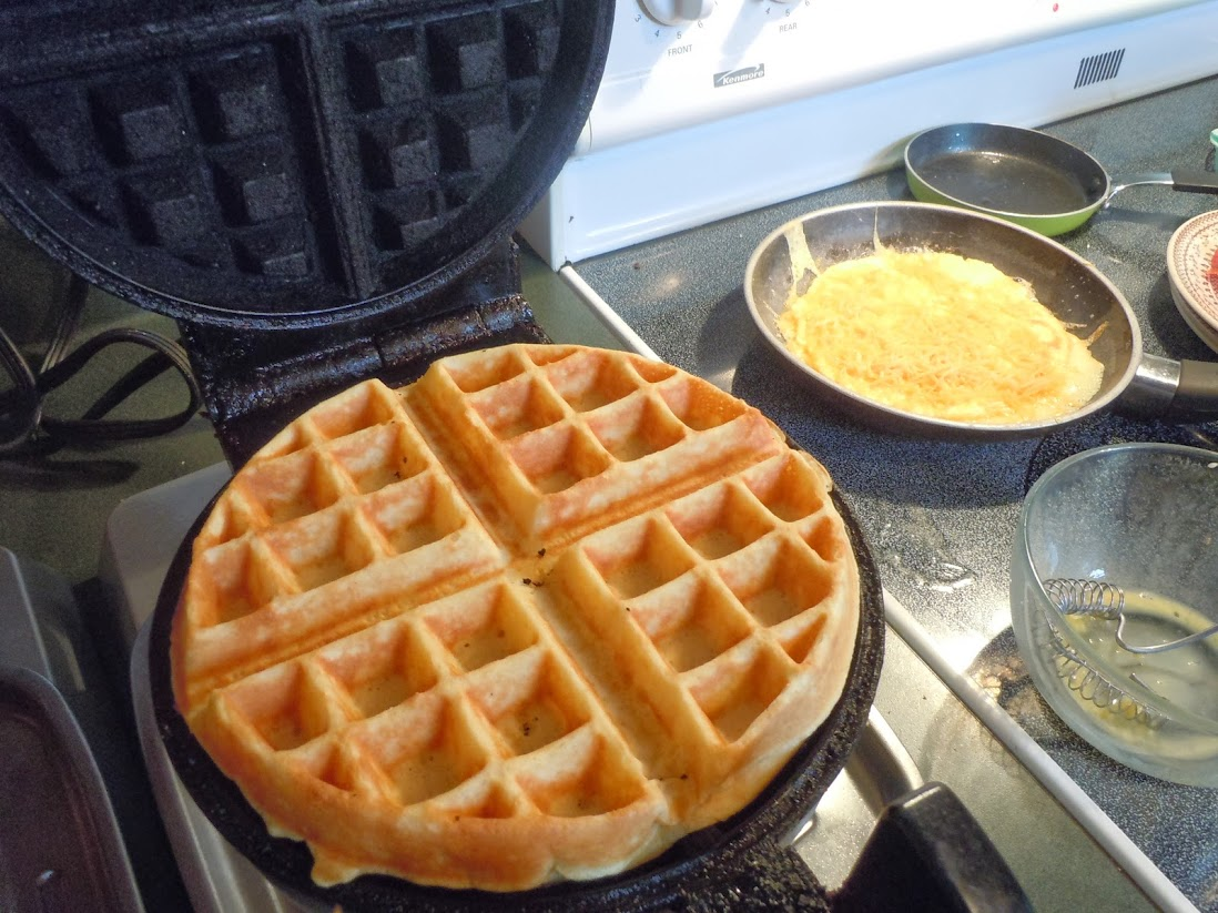 belgian waffle in the waffle maker next to a stove with eggs in a pan